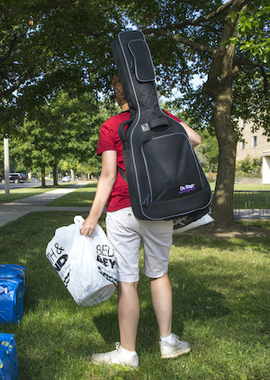 A student moving in to their residential hall with a musical instrument on their back.