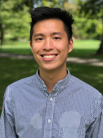 smiling male Asian student wearing blue checked shirt.