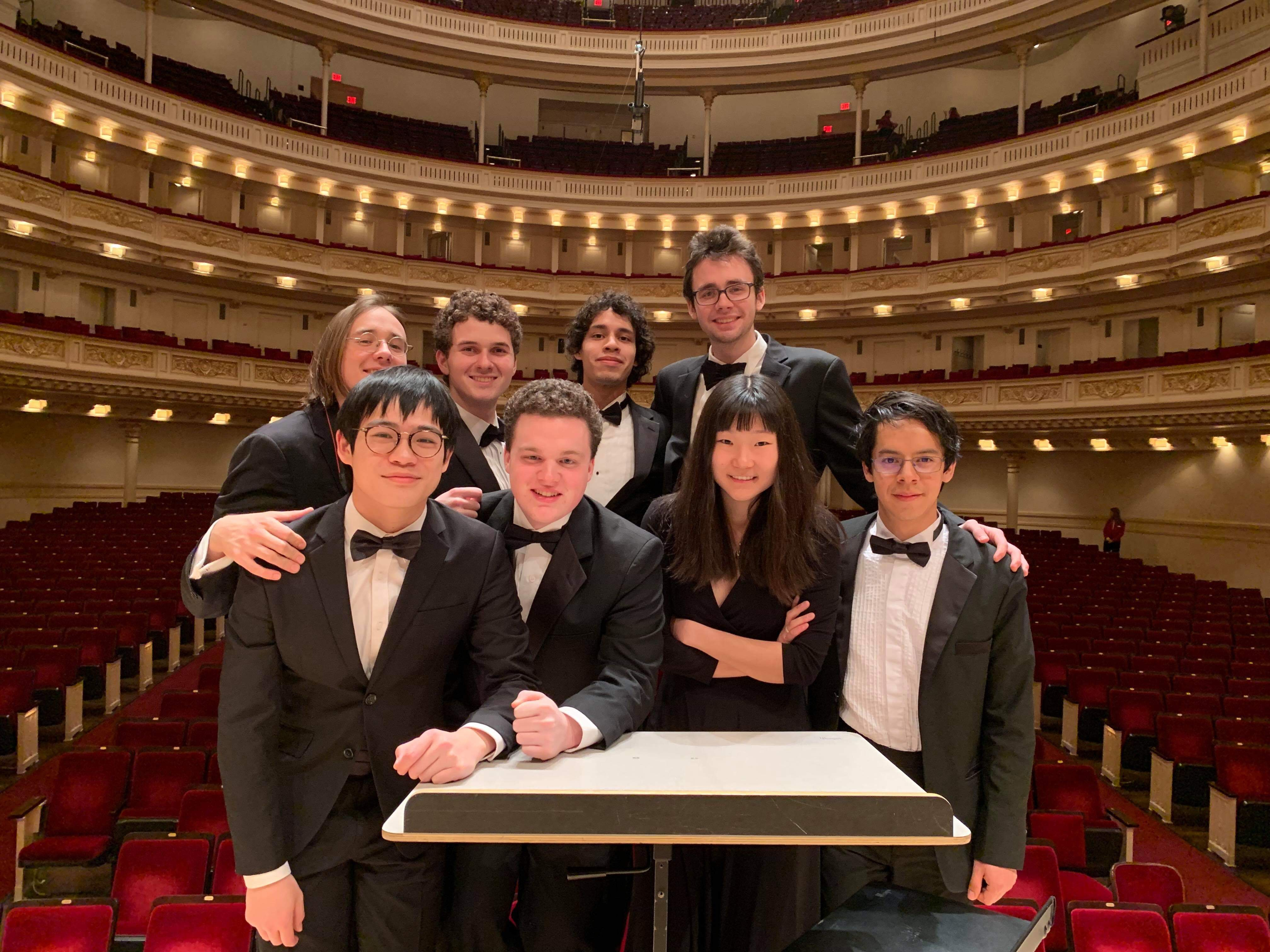 Eight percussionists standing at the conductor's podium in Carnegie Hall.