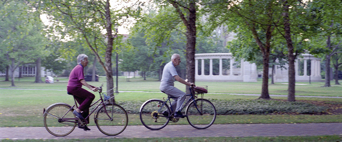 Two Kendal residents ride through Oberlin campus on bikes.