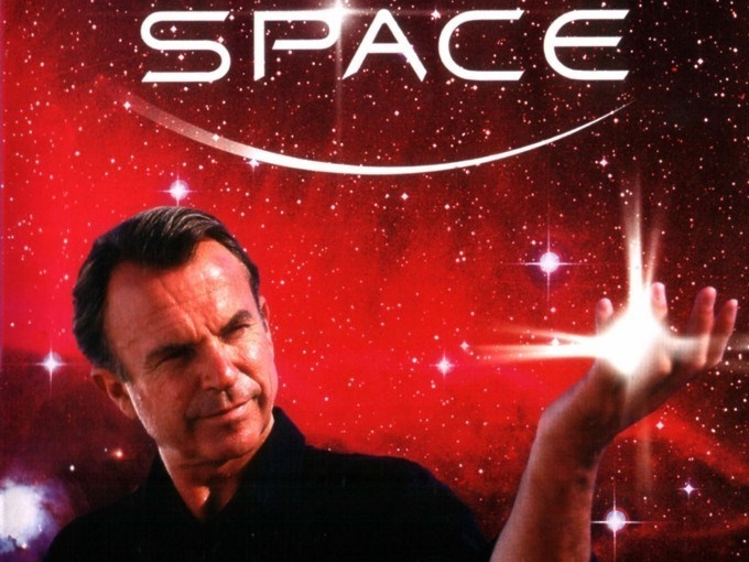 Actor Sam Neill holds an image of a galaxy in his hand