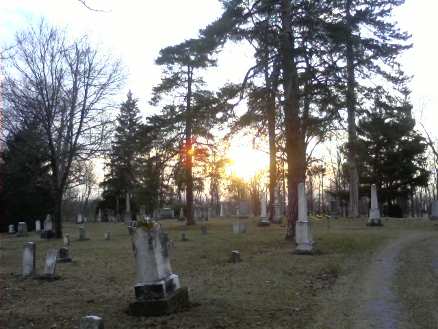 Old gravestones, with the sun over the horizon.