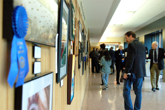 A crowd looks at the artwork hung in the hallway