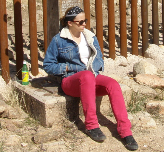 A student sits at the border wall