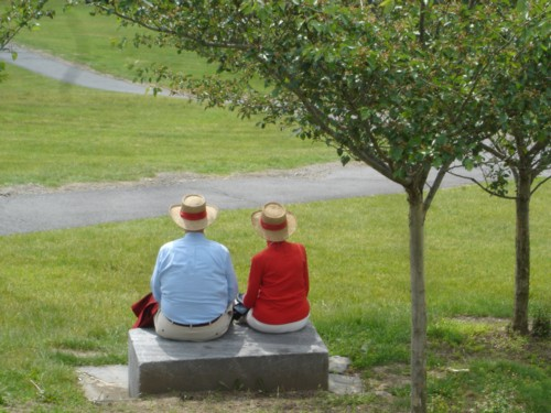 An older couple seated on a park bench