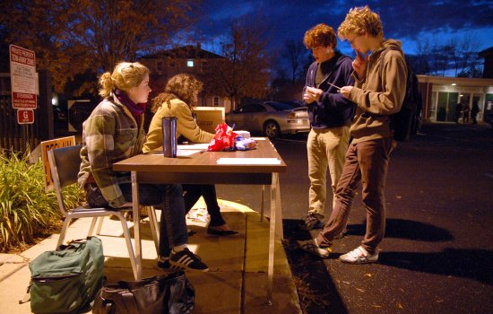Students sit at a registration table in the dark