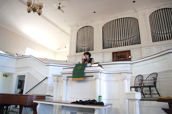 A professor speaking from behind the pulpit. She stands in front of a giant white organ