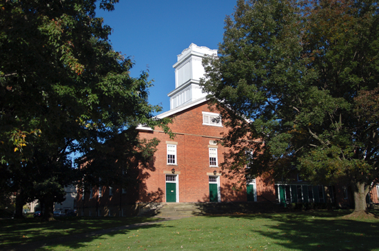 A view of First Church from the front. The building is brick and is shaped like a barn with a white tower