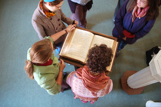 A group of students from above reading from a large Bible