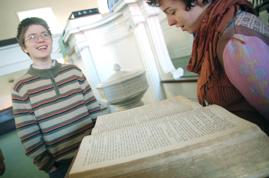 Two students in front of the pulpit reading from a large Bible