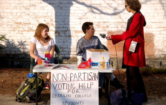 Students sit at a table and are being interviewed by a woman with a microphone