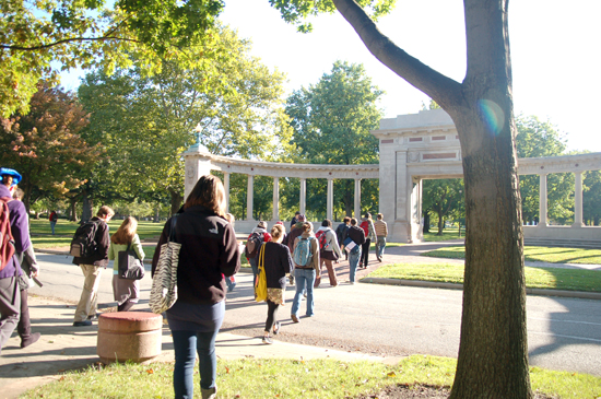A line of students from behind. They are walking toward the Memorial Arch in Tappan Square