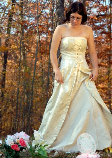 Student wearing a wedding dress in front of tree