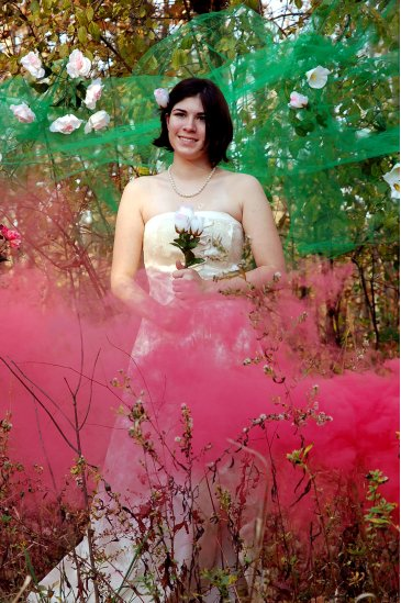 Student posing for a photo wearing a wedding dress and holding flowers, surrounded by pink and green smoke