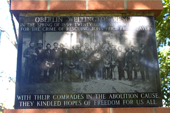 "A memorial with a picture of a large group of men posing. The title says: ""Oberlin Wellington Rescue. In the Spring of 1859 twenty Oberlinians went to jail for the crime of rescuing John Price from slavery."""