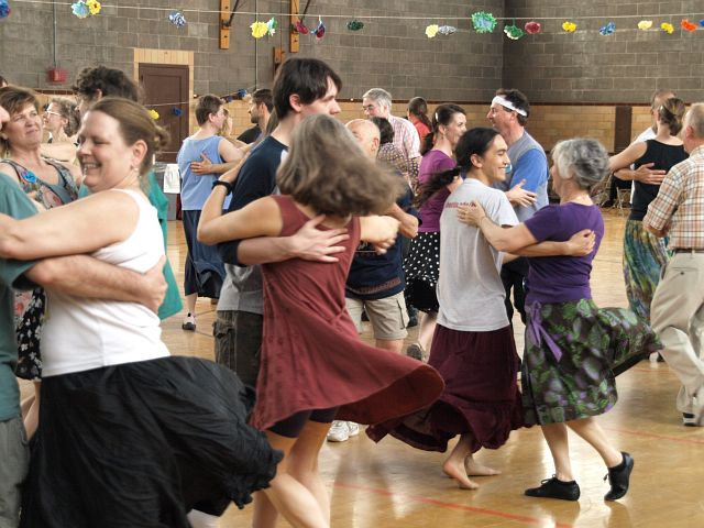 A gym full of couples contra dancing