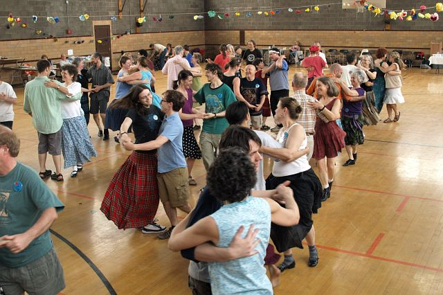 A gym full of partners contra dancing.