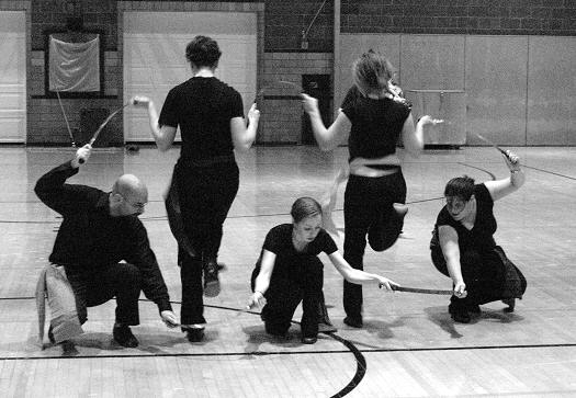 A dance group wearing all black mid dance, each holding swords
