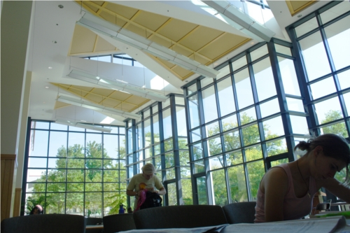 A student studies at a table in a very windowy, bright Science Center atrium