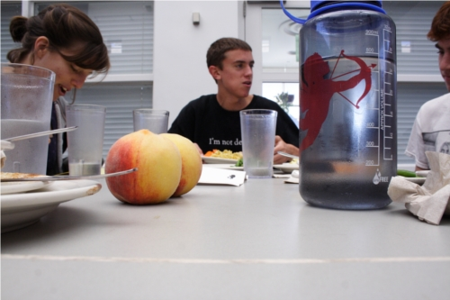 A table level view of a students sitting at a table in Stevie. In focus are two peaches and a Nalgene water bottle