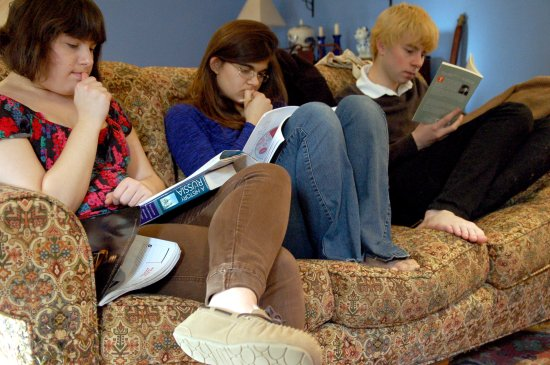 Students read textbooks on a couch
