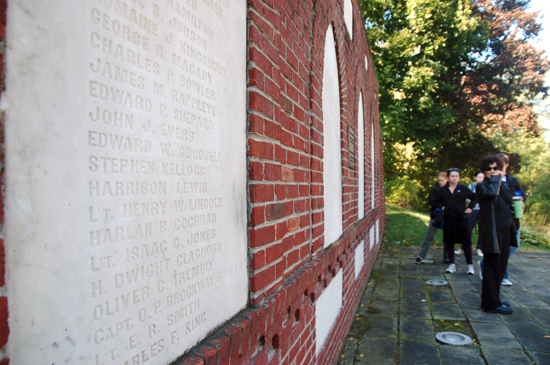 Students standing in front of the war memorial, which is a brick wall with concrete engravings of names