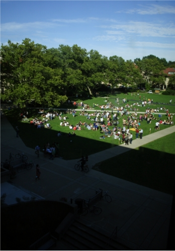 A view of wilder bowl from an upper floor of Mudd library. It is a sunny day and the grass is packed with lounging students