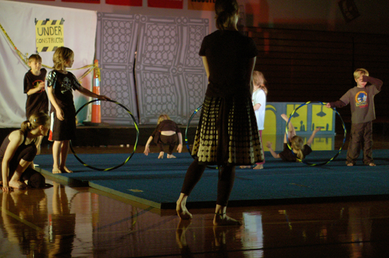 Children hold hoola hoops on a gym mat