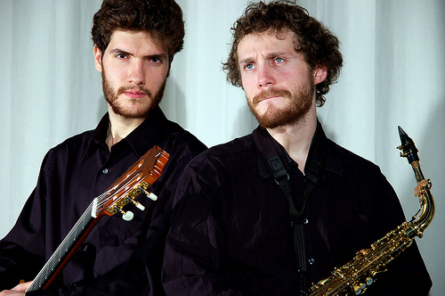 Two musicians posing for a photo holding a guitar and a saxophone
