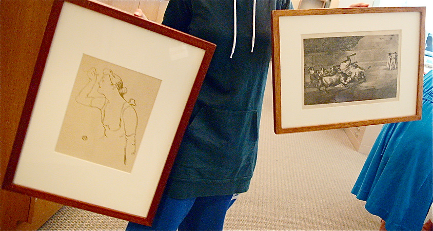 Alice holds up the two framed drawings