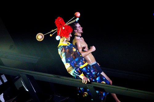 A performer wearing a red wig and a space themed dress. She is accompanied by a boy wearing only his underwear