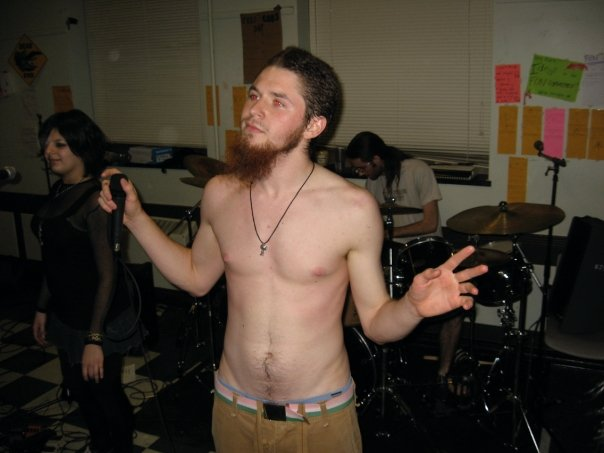 Grey is shirtless holding a microphone in front of a band