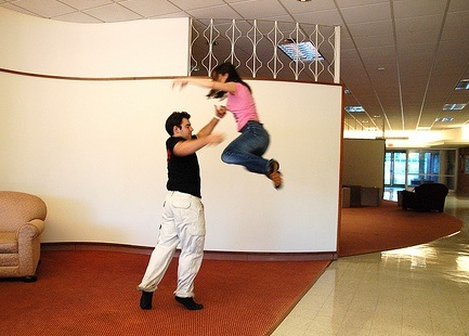 The man is propelling the girl into the air