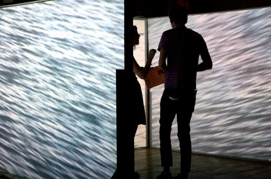 Two people stand in a room of screens featuring water