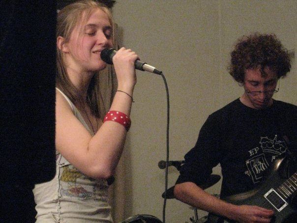 A girl singing into a microphone and a boy playing the guitar