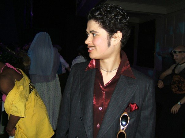 A student dressed as a drag king with a handlebar mustache and a blazer