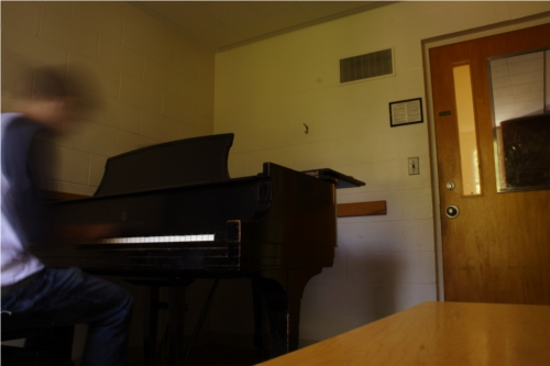 A student playing the piano in a conservatory practice room