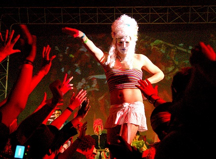 A performer on the Sco stage wearing a large white wig, a mini skirt, and a crop tank