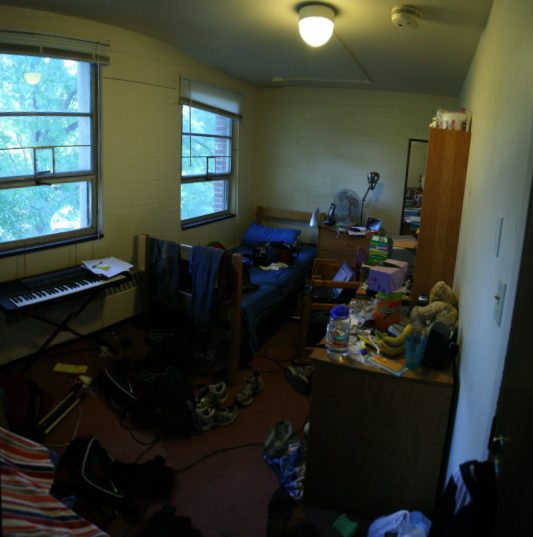 A messy dorm room with clothes on the floor and cluttered surfaces