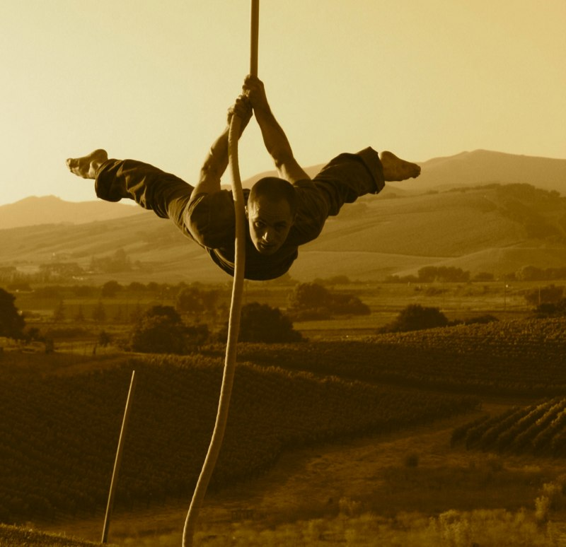 Man mid-air on a rope amidst farmland