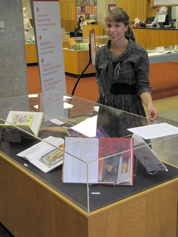 Alice shows a library display case containing several books