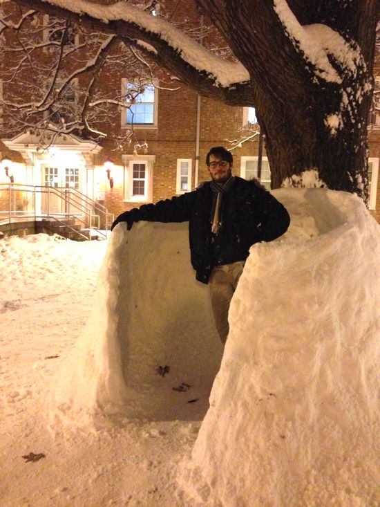 Student poses in a snow fort