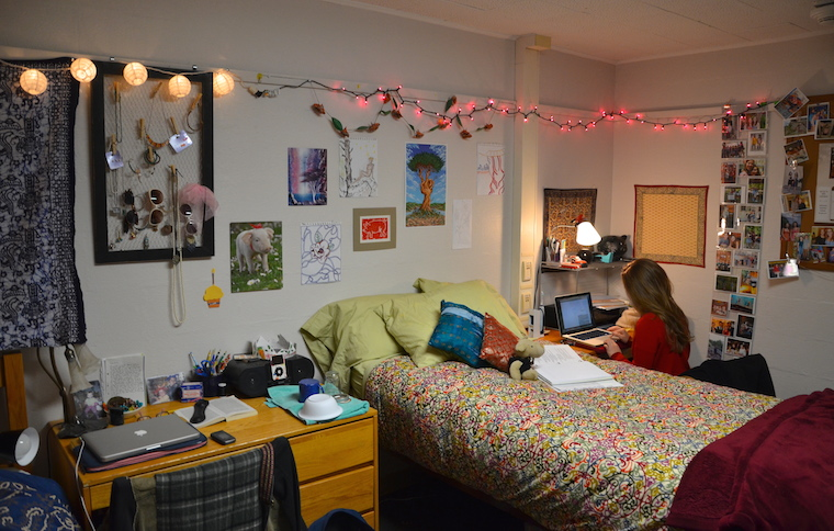 A girl sitting at her desk looking at a lap-top in a dorm room. The bed adjacent to her is made and lots of decorations hang on the wall.