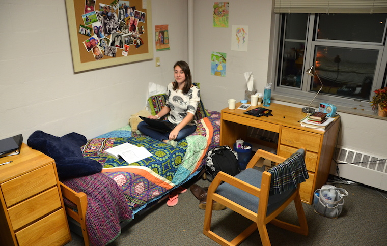 A girl sitting on her bed in a dorm room, looking at the camera. She has a textbook layed out in front of her.