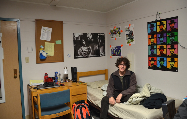 A boy is sitting on his bed in a dorm room. His bed is unmade and lots of posters hang behind him