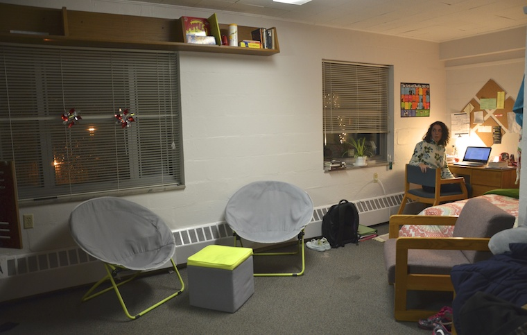 A student sitting at their desk in a dorm room looking back at the camera. This dorm looks different front the rest: much larger and with a different lay-out