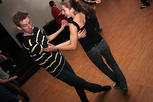 Two people practice dancing.