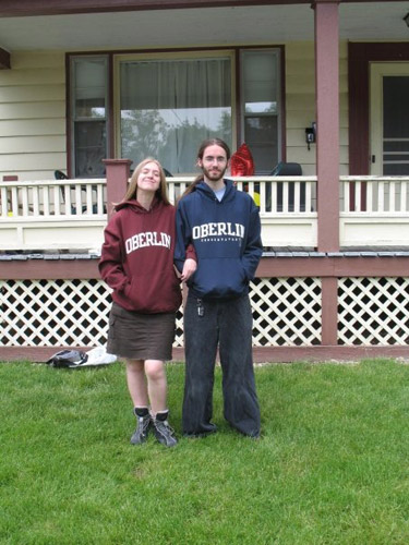Two people by a porch, wearing Oberlin sweatshirts