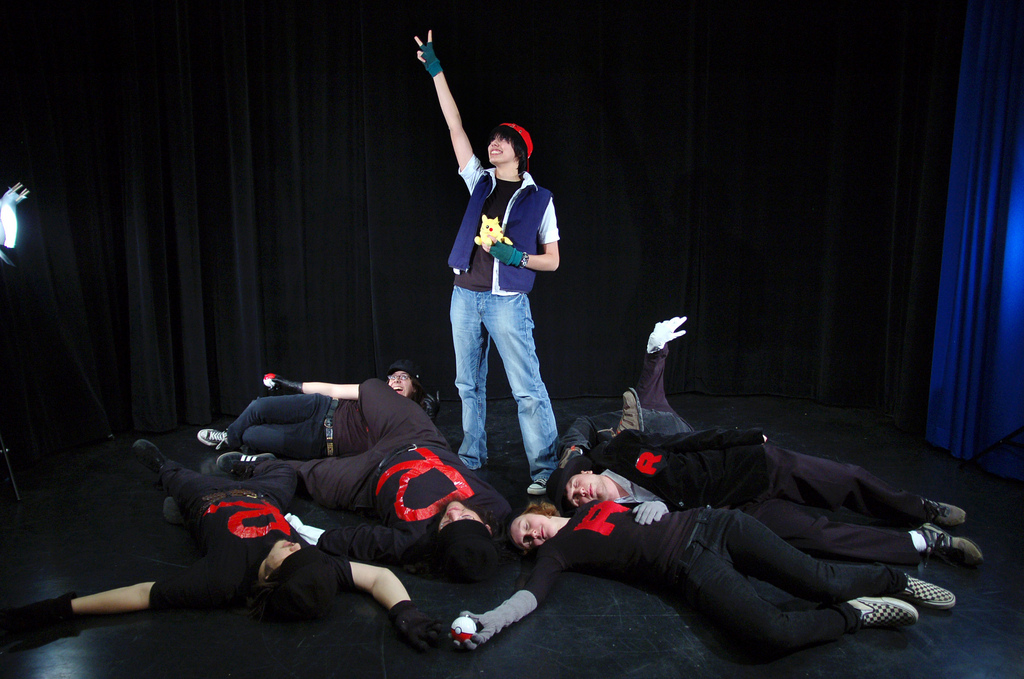 A group of people performing an act on a black stage. One person, dressed like Ash from Pokemon, stands in the middle with their arm raised towards the sky. Everyone else is dressed in black, is holding Pokemon balls, and is laying around Ash.