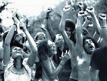 A crowd of people smiling with their arms raised in the air. Many have long hair and are not wearing shirts.